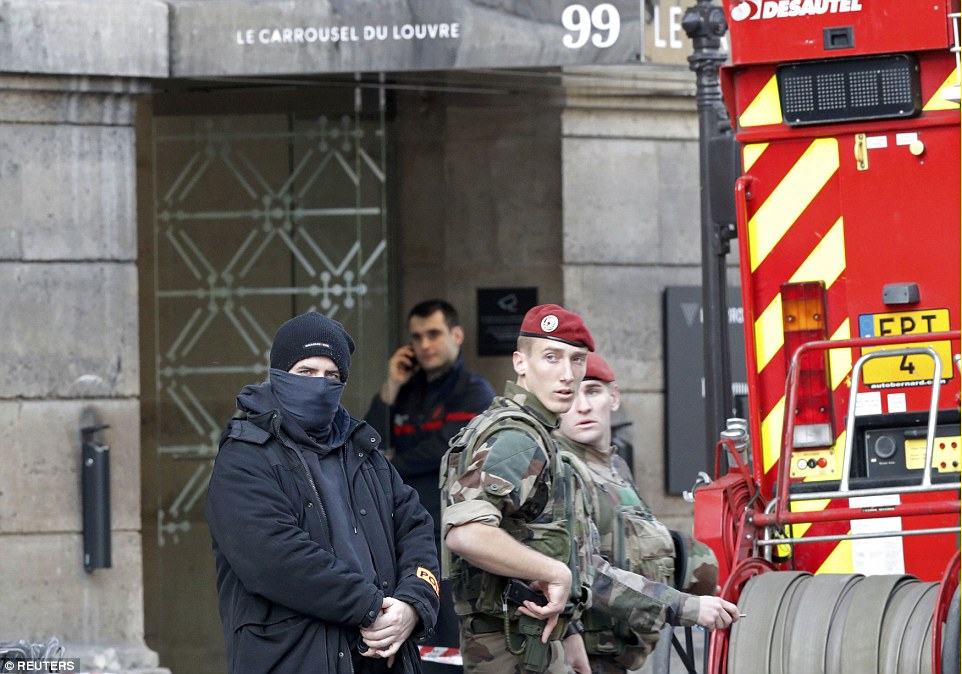 French police, soldiers and firefighters in front of the street entrance of the Carrousel du Louvre in Paris this morning after the attack