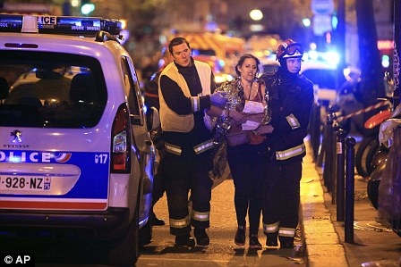 A woman is taken to safety following the horrific shootings on November 13, 2015, in which 130 people were killed