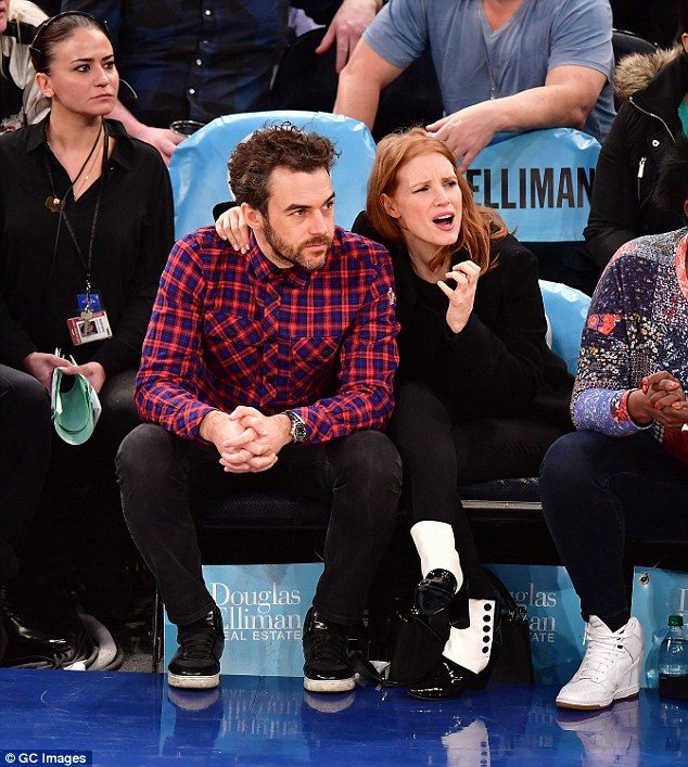 Devastated: The 39-year-old actress snuggled up to her handsome beau as she watched her team lose by 14 points on the night