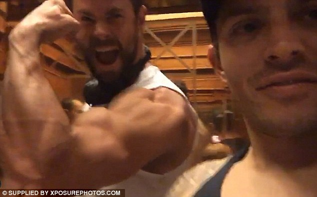 Give the fans the gun show:Chris' flashes his big cheeky grin and flexes his arm, making each muscle and vein visibly pronounced