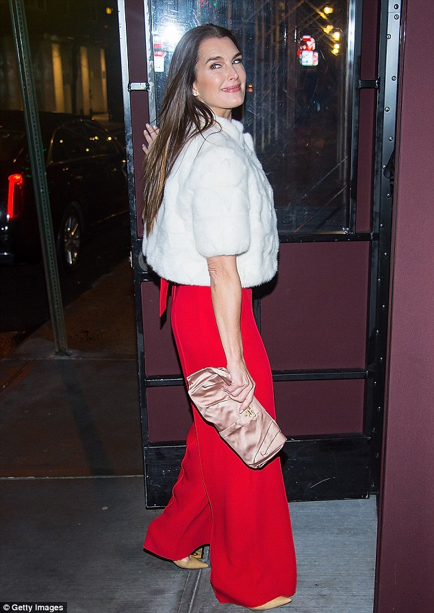 Hot mama:Shields, 51, wore a red strapless jumpsuit paired with nude pointed heels and a white, cropped fur jacket