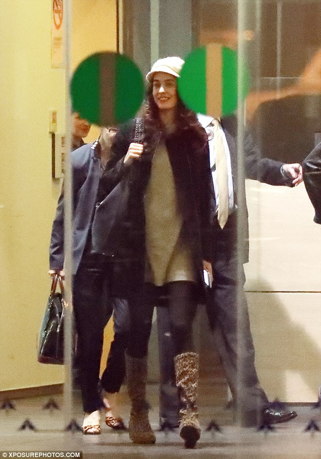 Beaming: Amal had a big smile on her face as she led the way out of the airport, wrapped up warm for the chilly weather