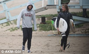 Chilly in the sand: The 27-year-old kept his hood over his head as his friend donned a wetsuit