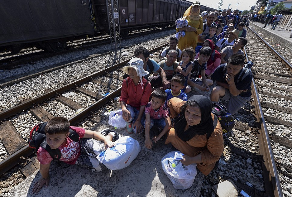 Here, migrants, mainly women and children, wait to board a train they hope will take them to a better place
