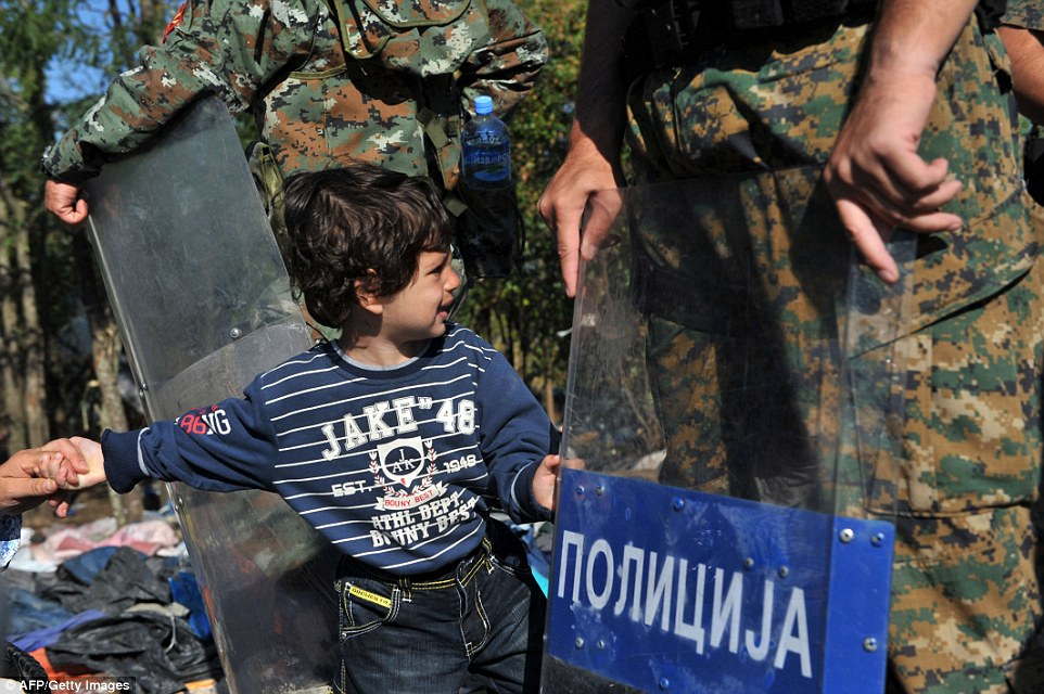This is one of the young migrants on his way to Serbia, today standing by the riot shields which were raised to block charging crowds earlier in the week but have now been lowered as the tension is released
