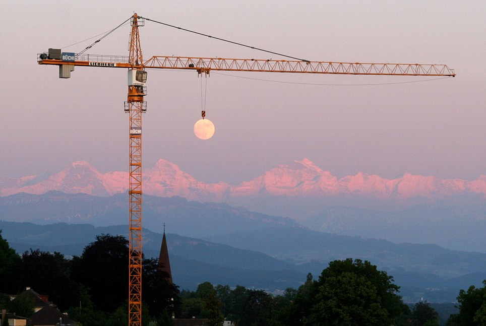Illusion: The moon looks like carried by a crane in this clever photo