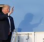 In this Friday, Feb. 10, 2017, photo, President Donald Trump waves to supporters on the steps of Air Force One as he arrives in West Palm Beach, Fla. Trump won't be filling out an NCAA Tournament bracket this March, unlike his predecessor, Barack Obama. (AP Photo/Wilfredo Lee)