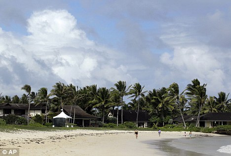 Exotic: People walk past a security tent on the beach at Kailua Bay not far from where Mrs Obama and her daughters are staying in Hawaii, on Sunday