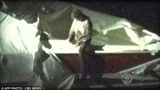 This image, taken from a surveillance camera shows Dzhokhar Tsarnaev climbing out of the boat on Friday evening after the climatic police gun battle