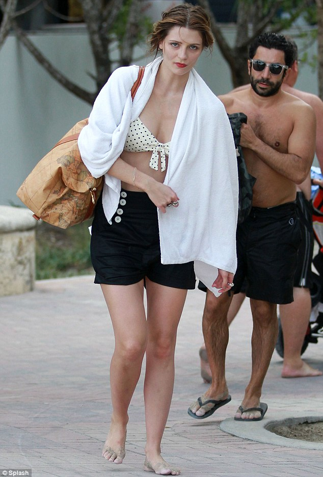 Covering up: Mischa leaves the beach with a white towel wrapped around her shoulders