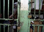 Inmates at Haiti's National Penitentiary in Port-au-Prince are living in overcrowded and filthy conditions. Pictured above, prisoners cram shoulder to shoulder to watch TV in their crowded cell inside the prison