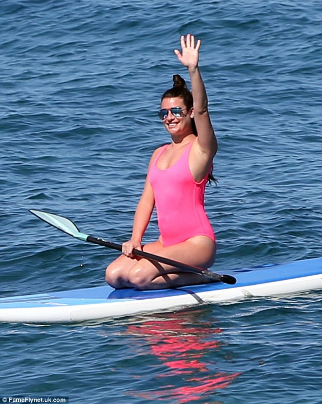 A warm hello:She'd been joined by friends for her day out, and appeared to be waving at one of them while she sat on the board, the paddle on her lap