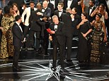 """The cast of """"Moonlight"""" and """"""""La La Land"""" appear on stage as presenter Warren Beatty (C), flanked by host Jimmy Kimmel (L) shows the winner's envelope for Best Movie """"Moonlight"""" on stage at the 89th Oscars on February 26, 2017 in Hollywood, California. / AFP PHOTO / Mark RALSTONMARK RALSTON/AFP/Getty Images"""
