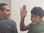 Miguel Alvarez-Flores (right) smiles and waves at news cameras in Houston court on Wednesday, as the gang leader known as 'Diabolico' and his partner 18-year-old Diego Hernandez-Rivera (left) facedcharges of aggravated kidnapping and murder