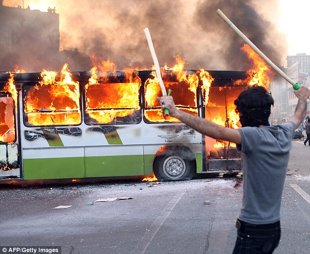 An Iranian protester stands next to a burning bus during clashes with Iranian police