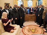 Counselor to the President Kellyanne Conway checks her phone after taking a photo as US President Donald Trump and leaders of historically black universities and colleges