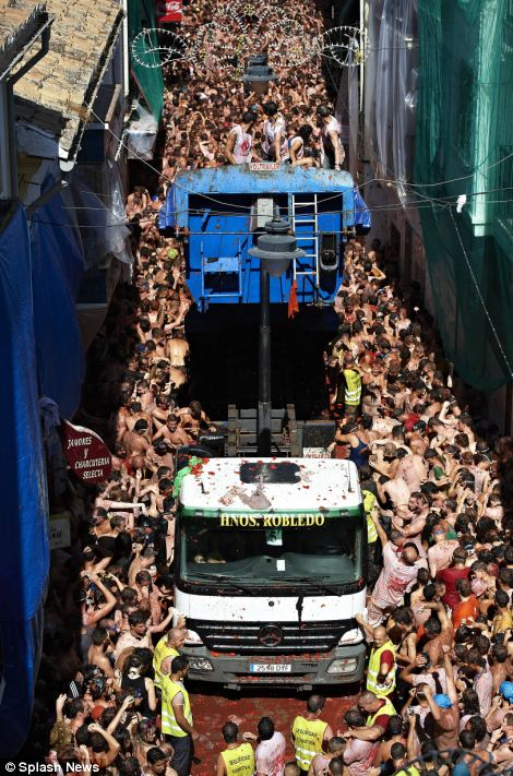 A truck loaded with tomatoes for the annual Tomatina festival in Bunol, Spain, eases its way through the crowds