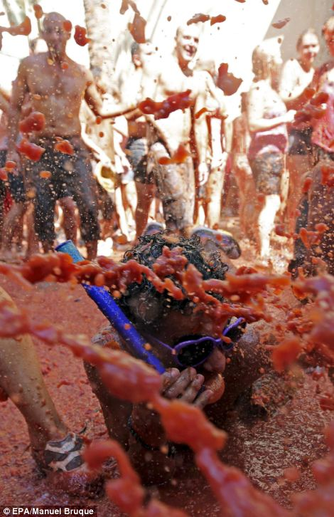 A man is splashed with more flying tomato pulp at La Tomatina
