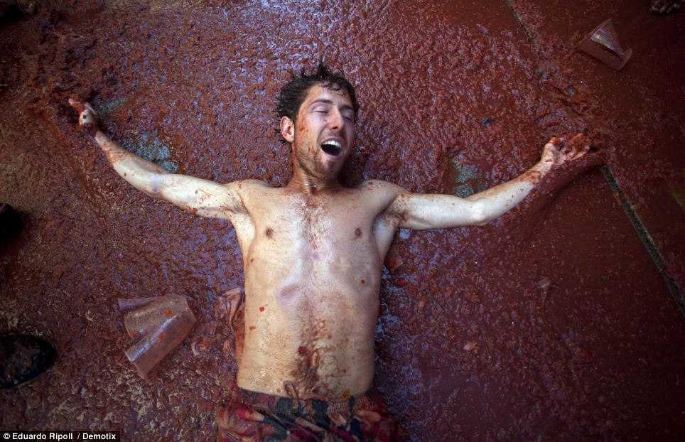 La Tomatina: A man lies flat on his back on a carpet of tomato pulp at the quirky Spanish festival