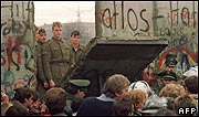 Crowds gather around hole in the Berlin Wall as East German guards look on