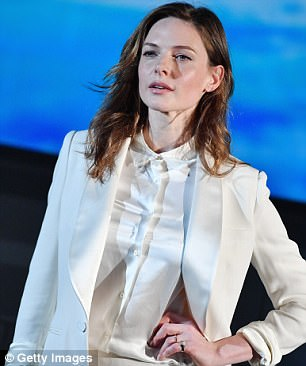 All white: Her sartorial look highlighted her slender figure as she slipped on a longline blazer with silk lapels while resting her ring decorated hand