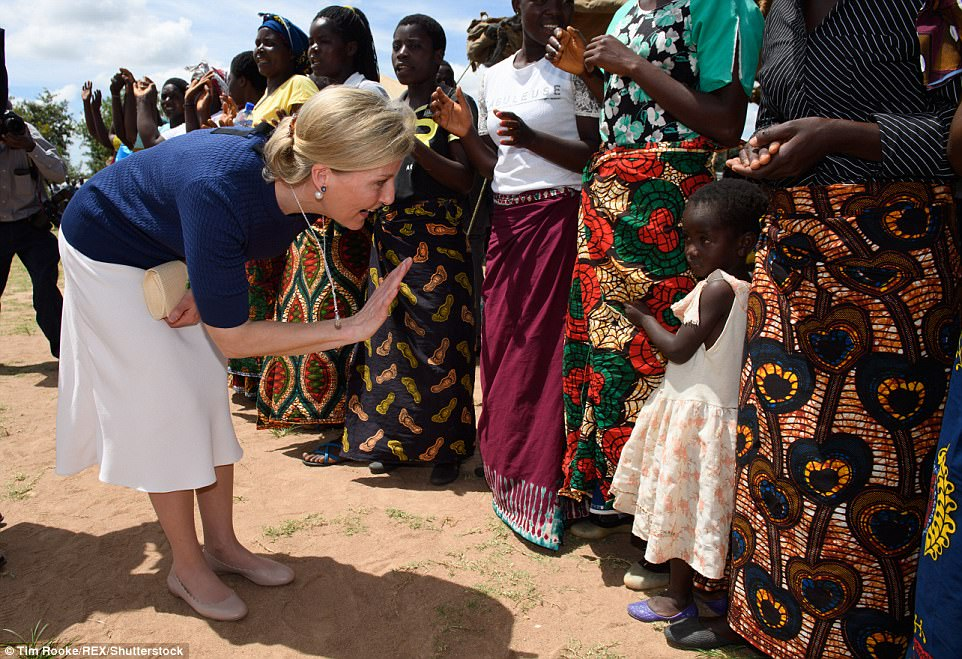 The Countess waves to a shy little girl clinging to her mother's skirts in the east African country