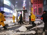 No-mageddon after all: Officials have downgraded the blizzard warning in New York City Tuesday to a winter storm warning. Above the 'Charging Bull' statue is covered in light snow in New York's Financial District on Tuesday