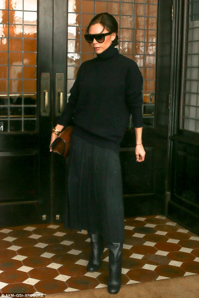 Chic and cheerful:Oozing glamour in a chic all-black ensemble, Victoria Beckham, 42, was a vision of beauty as she braved the adverse weather conditions in New York City on Tuesday