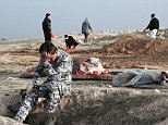 Harrowing pictures show the body of an unknown girl wrapped in a blanket after a mass grave of ISIS victims was discovered in Mosul