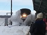 Here it comes: An Amtrak train is seen driving into snow, sending it flying on Wednesday