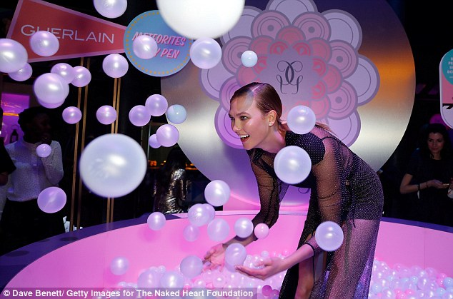 Light as air: Karlie Kloss had a fabulous time as she larked around in the ball pit at London's Fabulous Fund Fair in Camden on Tuesday night