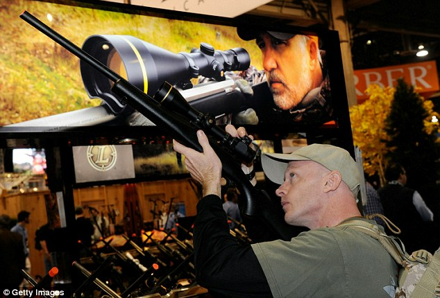 Aiming high: A man, one of 16,000 people at the convention, looks through the sights of a rifle