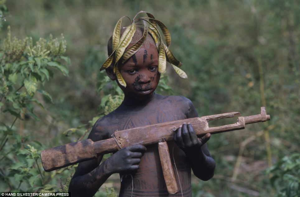 Sharp shooter: A young boy plays with a wooden gun. Although the tribes' rustic lifestyles are far removed from modern towns and cities influences have crept in