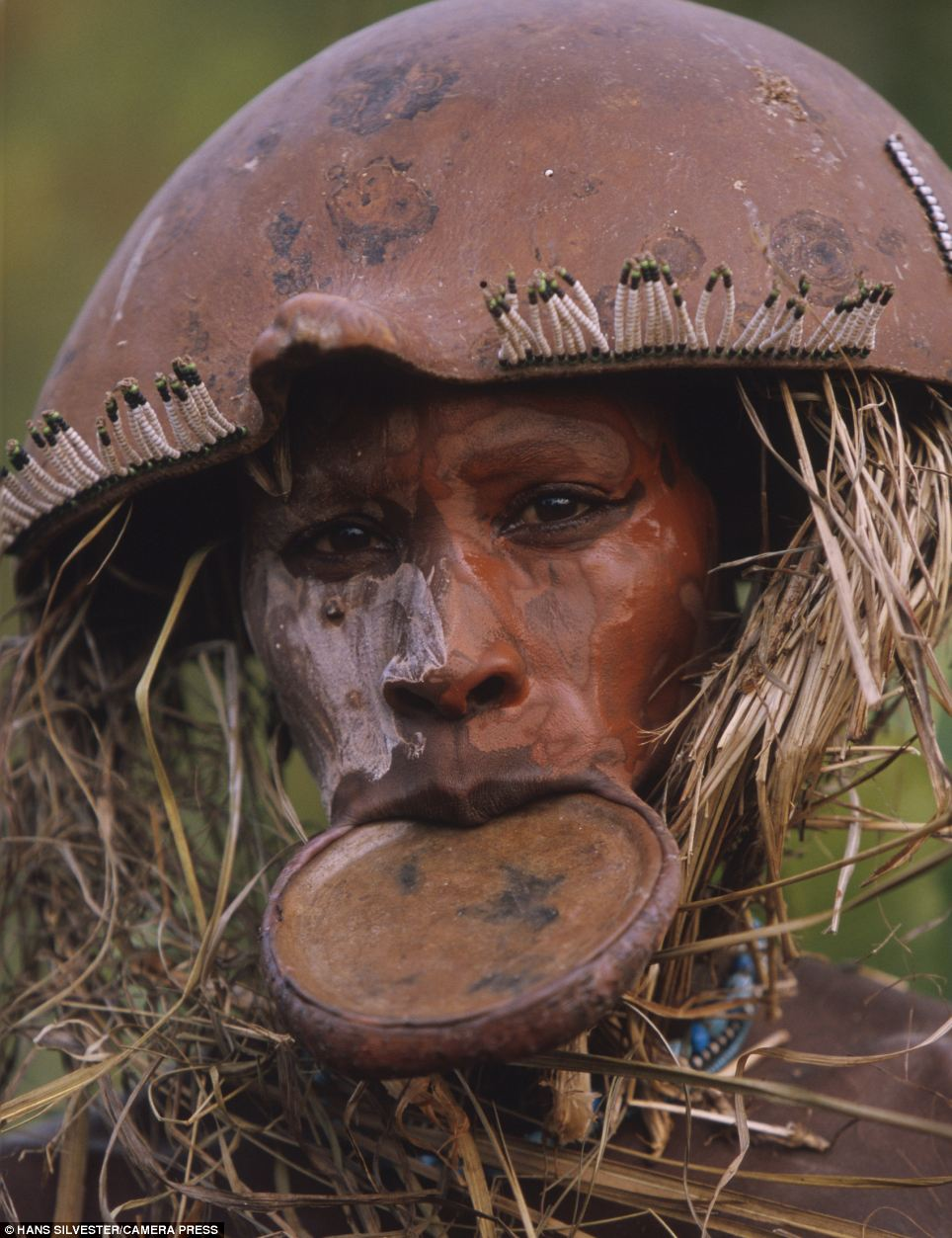 Tribal: This man wears a traditional mouth plate with his straw-covered beaded headdress