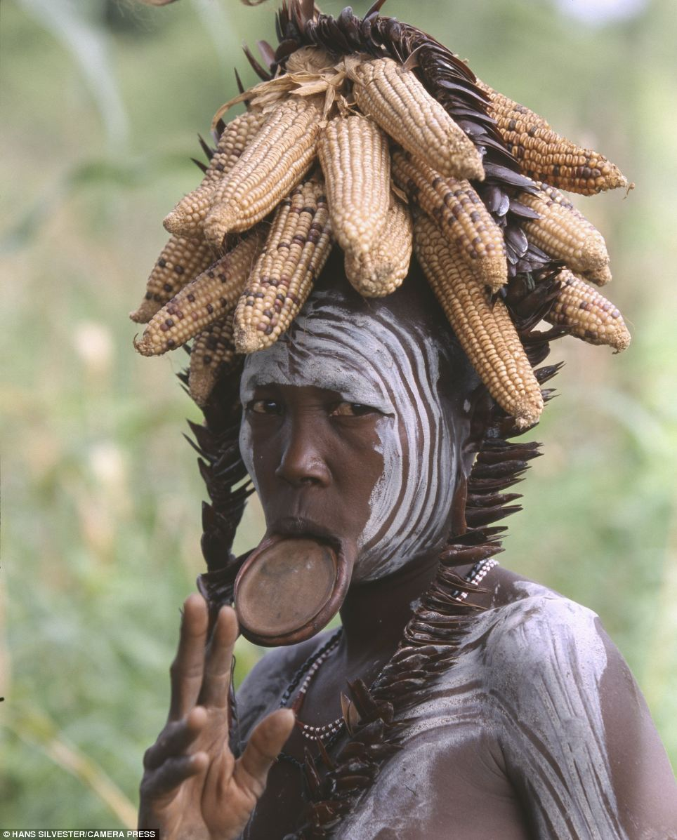 Traditional: A woman with her face painted in white circles wears a crown of dried corn and a mouth plate
