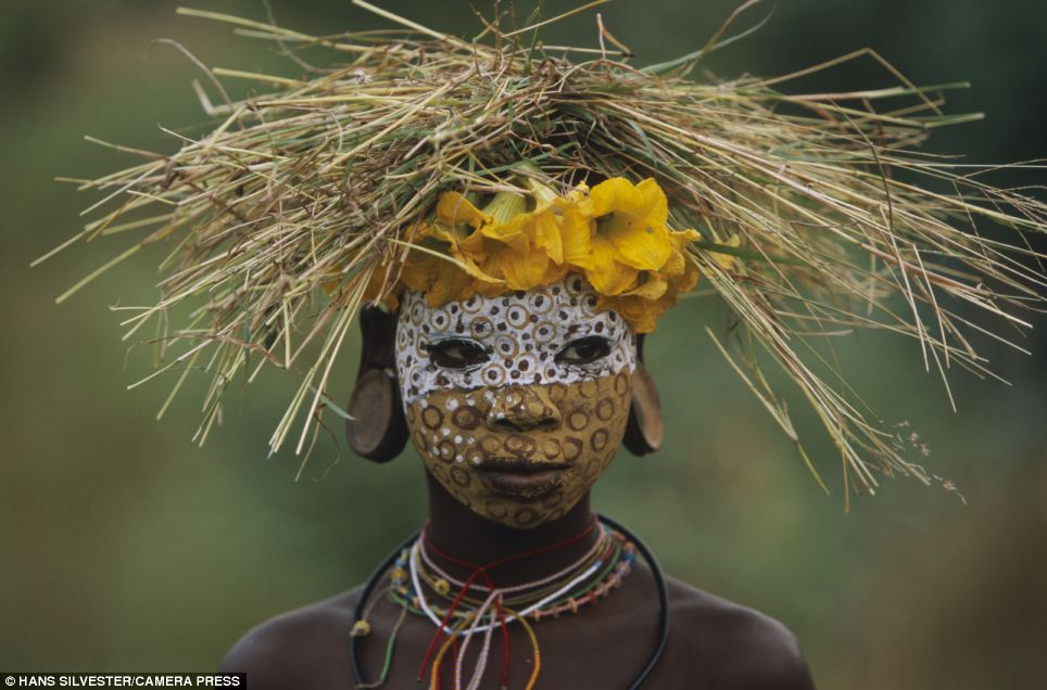 Illustrated: The book highlights the ways of the Omo tribes who live close to nature with their painted faces, scarified bodies and extravagant headdresses with plants and feathers cleverly combined