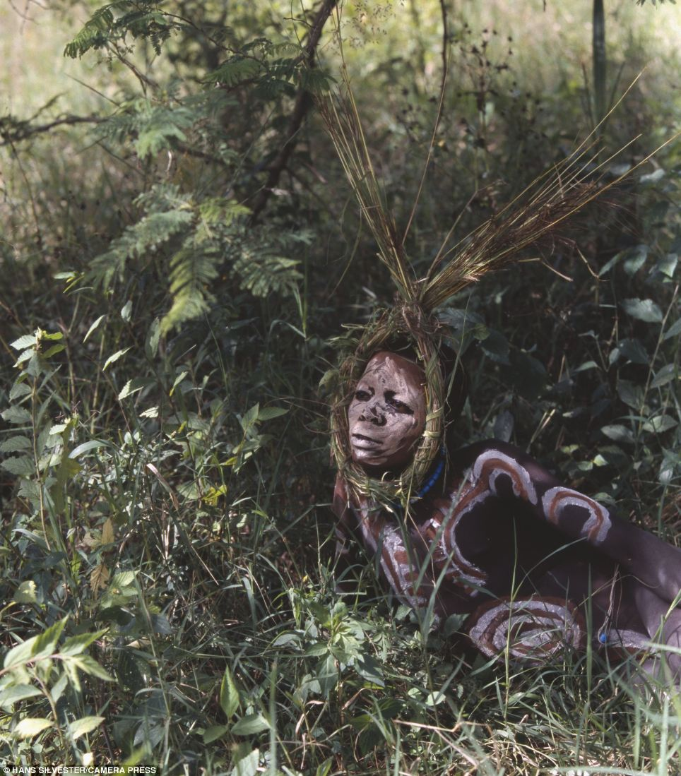 Secret: Despite his painted body this man manages to blend in amongst the Ethiopian vegetation
