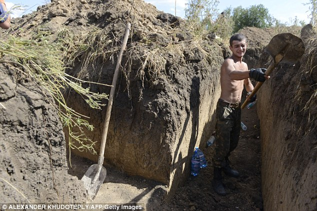 An Ukrainian soldier digs a trench on the outskirts of the southern Ukrainian city of Mariupol today. Nato chief Anders Fogh Rasmussen urged Russia  to halt its 'illegal' military actions in Ukraine