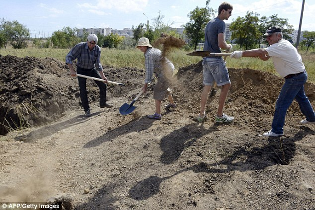 Digging in: Civilians dig trenches and make fortifications with sandbags as they assist Ukrainian troops in organising their defence on the outskirts of the southern Ukrainian city of Mariupol