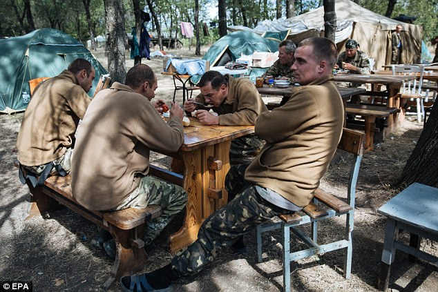 Rest: Ukrainian servicemen rest at their military camp near the eastern Ukrainian city of Debalcevo, in Ukraine. Mr Putin today asked pro-Moscow rebels to open a 'humanitarian corridor' to allow Ukrainian soldier who remain hemmed in to the region to go home