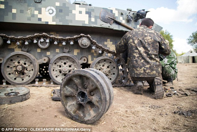 Ukrainian servicemen repair a part of their MPC inside a military camp in Donetsk