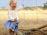 A mother taking photos of her two-year-old in outback Australia has snapped an incredible picture of a massive brown snake slithering past her daughter's leg