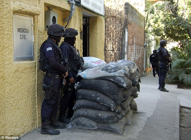 Lockdown: Police shelter behind sandbags as they guard the Federal Commission of Electricity during the raid