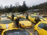 Hundreds of bright yellow cars flooded a Cotswold village today in support of a pensioner whose motor was branded an 'eyesore'