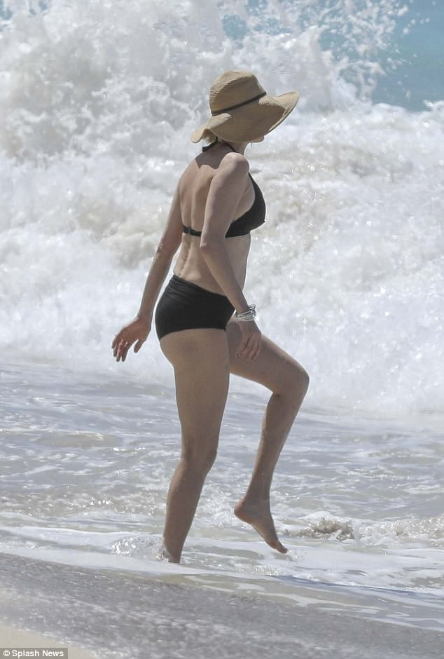 Making a splash: The Hollywood star highlighted her trim, athletic figure in the practical and minimalist swimwear as she ventured into the sea