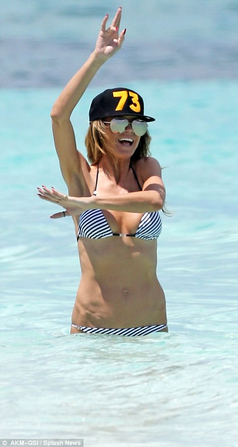 Throw your hands in the air like you just don't care: Heidi appeared to be having a whale of a time in the surf