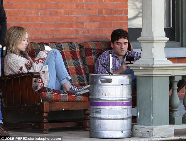 Downtime: The beauty looked relaxed and looked at her notes while Oscar checked his phone