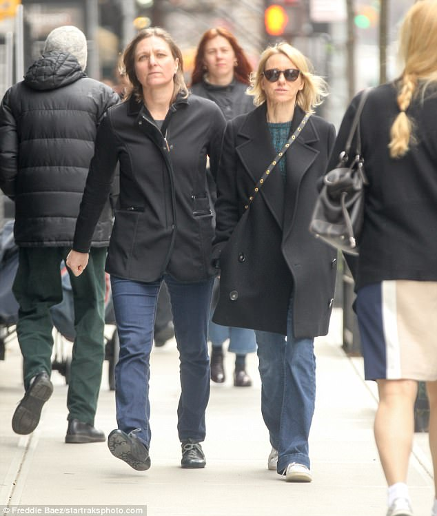 Rugged up: Both Naomi and her pal cut casual figures in a pair of blue jeans with a black coat, opting for comfortable sneakers as they strolled through the city