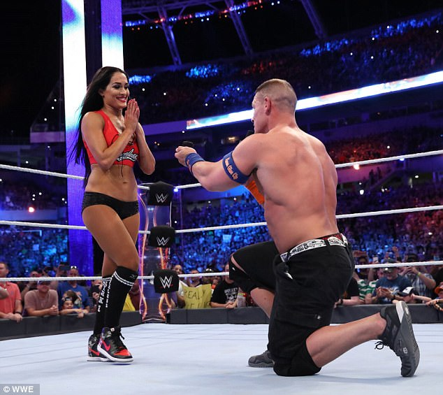 Popping the question: This is the moment John, 39, got down on one knee after the couple defeated foes The Miz and Maryse