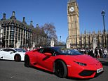 A Bentley and a Lamborghini come to a stop outside the Palace of Westminster as several other supercars line up behind them